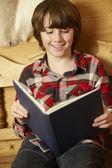 年轻的男孩坐在木制座椅读的书 — 图库照片