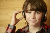 Young Boy Sitting On Wooden Seat Listening To MP3 Player — Stock Photo
