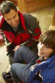 Ojciec pomoc syna, aby umieścić na ciepłe zewnątrz ubrania i buty — Zdjęcie stockowe