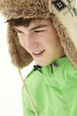 Portrait Of Teenage Boy In Snow Wearing Fur Hat — Stock Photo