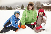 Group Of Children Building Snowman Wearing Woolly Hats — Stock Photo