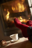 Close Up Of Mans Feet Relaxing By Cosy Log Fire With Tea And Cak — Stock Photo