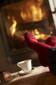 Gros plan du mans pieds relaxants par cheminée confortable avec thé et cak — Photo