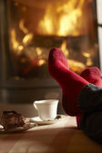Close Up Of Mans Feet Relaxing By Cosy Log Fire With Tea And Cak — Stockfoto