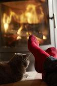 Zblízka na mans nohou relaxační tím útulným krbem s kočkou — Stock fotografie