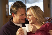 Middle Aged Couple Sitting On Sofa With Hot Drinks — Stok fotoğraf