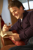 Middle Aged Man Relaxing With Book Sitting On Sofa Drinking Whis — Stock Photo