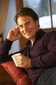 Middle Aged Man Relaxing With Hot Drink On Sofa — Stockfoto