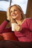 Středního věku žena relaxační s horkým nápojem na pohovce u televize — Stock fotografie