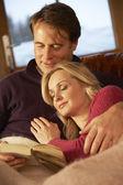 średniej wieku para relaksujący na kanapie w domek z widok zima — Zdjęcie stockowe