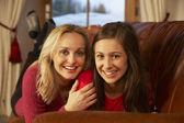 Anne ve kızı beraber kanepede rahatlatıcı portresi — Stok fotoğraf