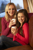 Portrait Of Mother And Daughter Relaxing On Sofa Together With H — Stock Photo