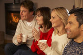 Group Of Middle Aged Couples Sitting On Sofa With Hot Drinks Wat — Stock Photo