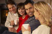 Group Of Middle Aged Couples Sitting On Sofa With Hot Drinks Tal — Stock Photo