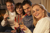 Group Of Middle Aged Couples Sitting On Sofa With Champagne — Stock Photo