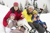 Familjen äter smörgås på skidsemester i bergen — Stockfoto