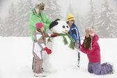 Grupo de crianças em construção de boneco de neve em férias de esqui nas montanhas — Fotografia Stock