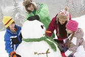 集团的雪人滑雪度假建筑在山中的儿童 — 图库照片