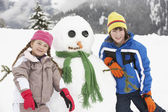Two Young Children Building Snowman On Ski Holiday In Mountains — Stock Photo