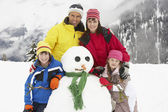 Family Building Snowman On Ski Holiday In Mountains — Stock Photo