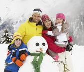 Familie gebouw sneeuwpop op skivakantie in bergen — Stockfoto