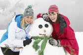Two Female Friends Building Snowman On Ski Holiday In Mountains — Stock Photo
