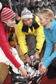 Sales Assistant Helping Couple To Try On Ski Boots In Hire Shop — Stock Photo