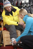 Sales Assistant Helping Man To Try On Ski Boots In Hire Shop — Stock Photo