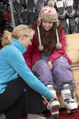 Sales Assistant Helping Teenage Girl To Try On Ski Boots In Hire — Stock Photo