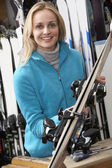 Female Sales Assistant With Skis In Hire Shop — Stock Photo