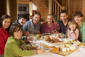 Two Familes Enjoying Meal In Alpine Chalet Together — Stok fotoğraf
