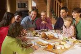 Två familes njuter måltid i alpin chalet tillsammans — Stockfoto