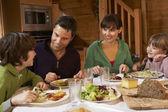 Família desfrutar a refeição no chalé alpino juntos — Foto Stock