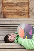 Teenage Boy With Snowboard On Ski Holiday Lying On Wooden Bench — Stock Photo