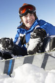 年轻的男孩坐在雪与单板滑雪 — 图库照片