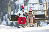 Mother And Daughter Getting Off chair Lift On Ski Holiday In Mou — Stockfoto