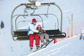 Mother And Daughter Getting Off chair Lift On Ski Holiday In Mou — Zdjęcie stockowe