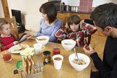 Genitori portando via gadget da bambini mentre mangiare breakfas — Foto Stock