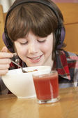 Boy Listening To MP3 Player Whilst Eating Breakfast — Stock Photo