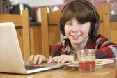 Boy Using Laptop Whilst Eating Breakfast — Stock Photo