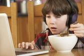 Boy pomocí notebooku, zatímco jíst snídani — Stock fotografie