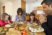 Family Saying Grace Before Eating Lunch Together In Kitchen — Stock Photo