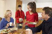 Nuttige tiener kinderen eten serveren aan ouders in keuken — Stockfoto