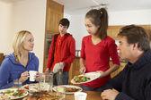 Nutteloze tiener clearing omhoog na familie maaltijd in keuken — Stockfoto