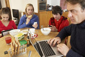Teenage Family Using Gadgets Whilst Eating Breakfast Together In — Stock Photo