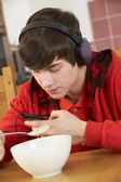 Teenage Boy Listening To MP3 Player Whilst Eating Breakfast — Stock Photo