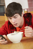 Teenage Boy Teenage Texting Whilst Eating Breakfast — Stok fotoğraf