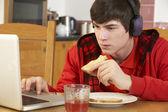 Adolescent utilisant l'ordinateur portable en mangeant le déjeuner — Photo