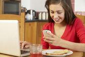 十几岁的女孩在吃饭的时候 breakfa 使用笔记本电脑和移动电话 — 图库照片