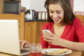 Teenage Girl Using Laptop And Mobile Phone Whilst Eating Breakfa — Zdjęcie stockowe